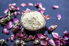 Organic and herbal face pack of Honey & Gram flour with its thick liquid mixture and some rose petals for good aroma on wooden sur. Face used to cure acne & royalty free stock photography