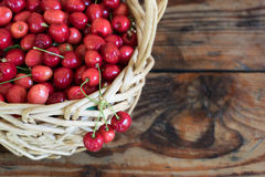 organic homegrown cherries in a basket, on wooden background stock images