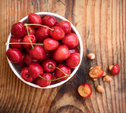 organic homegrown cherries and stones in a vintage ceramic bowl, on wooden background Royalty Free Stock Image