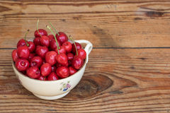 Organic homegrown cherries in a vintage ceramic bowl, on wooden background royalty free stock photo