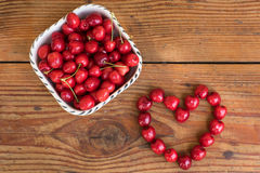 Organic homegrown cherries on wooden background in heart shape Stock Photography