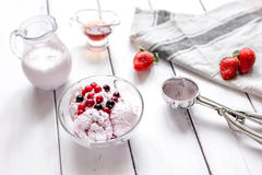 Organic homemade ice cream in glass bowl on wooden background. Organic homemade ice cream with strawberry in glass bowl on wooden background Royalty Free Stock Photography