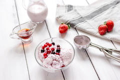 Organic homemade ice cream in glass bowl on wooden background. Organic homemade ice cream with strawberry in glass bowl on wooden background Royalty Free Stock Photos