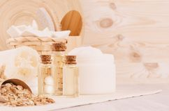 Organic homemade white cosmetics, bottles with oil and raw oatmeal flakes, bath accessories on light beige wooden background. Royalty Free Stock Photography