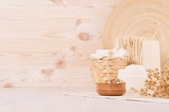 Organic homemade white cosmetics and raw oatmeal flakes, bath accessories on light beige wooden background, border. Royalty Free Stock Photos