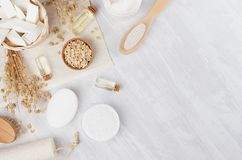 Organic homemade white cosmetics and raw oatmeal flakes, massage oil, bath accessories on light beige wooden background, flat lay. Organic homemade white stock image