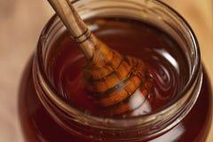 Organic honey drips from wooden dipper in jar. Closeup photo Stock Photo
