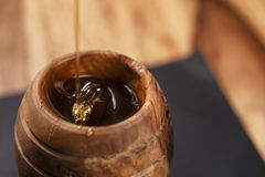 Organic honey drips from wooden dipper in jar. Closeup photo Royalty Free Stock Images