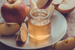 Organic honey in glass jar and red apple on the plate Royalty Free Stock Images