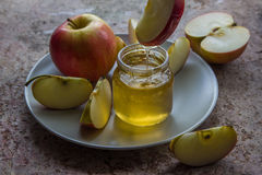 Organic honey in glass jar and red apple on the plate Stock Images