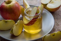 Organic honey in glass jar and red apple on the plate Stock Photography
