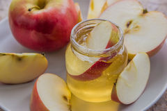 Organic honey in glass jar and red apple on the plate Royalty Free Stock Photo