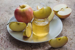 Organic honey in glass jar and red apple on the plate Stock Photos