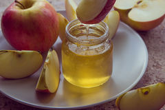 Organic honey in glass jar and red apple on the plate.  Stock Image