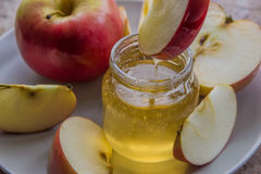 Organic honey in glass jar and red apple on the plate.  Stock Photo