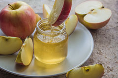 Organic honey in glass jar and red apple on the plate.  Stock Images