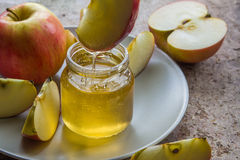 Organic honey in glass jar and red apple on the plate.  Royalty Free Stock Photography