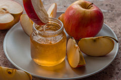 Organic honey in glass jar and red apple on the plate.  Royalty Free Stock Image