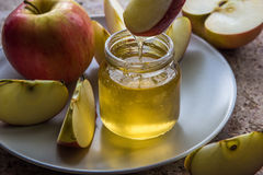 Organic honey in glass jar and red apple on the plate.  Royalty Free Stock Photos