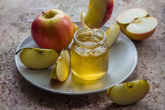 Organic honey in glass jar and red apple on the plate.  Royalty Free Stock Images