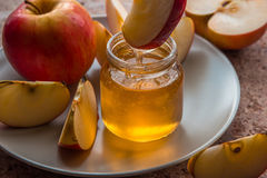 Organic honey in glass jar and red apple on the plate.  Royalty Free Stock Photo