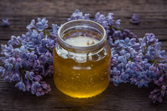 Organic honey in glass jar surrounded by spring blossom purple l. Ilac Stock Photos