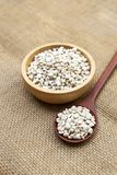 Organic Job`s tears seed in round wooden bowl and wooden spoon on hessian fabric background. Natural product, vegetarian food stock photos