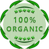 100% organic label. 100 percent organic badge on white background with leaves and a striped background stock illustration