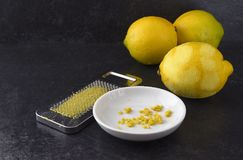 Organic lemon fruit, freshly grated peel or rind and the metal g royalty free stock photo