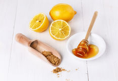Organic lemons with honey and brown sugar over white background Stock Photos