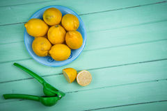 Organic lemons and juice squeezer on table Stock Photo