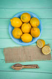 Organic lemons and juice squeezer on table Royalty Free Stock Images