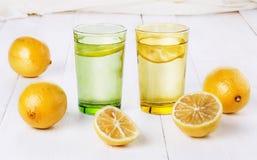 Organic lemons and lemonade over white background. Group of organic lemons and lemonade over white wooden background. Selective focus, shallow DoF royalty free stock photos