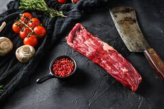 Organic machete or hanger butcher steak, near butcher knife with pink pepper and rosemary. Black background. Top view. side view