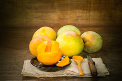 Organic mangos. Still life with group of organic mangos on wooden background Stock Photography