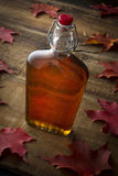 Organic Maple Syrup. On wooden background with maple leaves Stock Photos