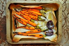 Organic meal with carrots and onion grilled in the oven royalty free stock images