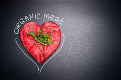 Organic meat for healthy Eating. Heart shape raw meat with herbs and text on black blank chalkboard background Stock Photography