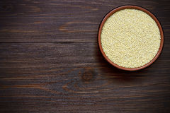 Organic millet in bowl on wooden table. Uncooked organic millet in ceramic bowl on wood Stock Photos