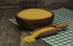 Organic millet seeds in a bowl on wooden table Stock Image