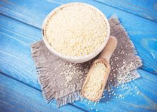 Organic millet seeds in a ceramic bowl on blue wooden table. royalty free stock photography