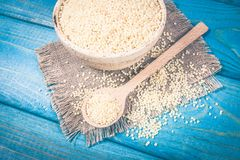 Organic millet seeds in a ceramic bowl on blue wooden table. stock photos
