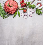 Organic Minced Meat with cooking ingredients , wooden spoon and spices mortar  on gray stone background, top view. Place for text. Meat food Stock Images