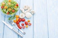 Organic mushrooms. Health food. Fresh mushrooms and arugula salad, cherry tomatoes royalty free stock photo