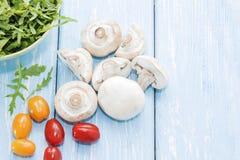 Organic mushrooms. Health food. Fresh mushrooms and arugula salad, cherry tomatoes stock photography