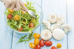 Organic mushrooms. Health food. Fresh mushrooms and arugula salad, cherry tomatoes royalty free stock photography