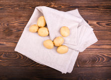 Organic new potatoes. Close up of raw and organic new light brown potatoes on a grey fabric and on a dark brown wooden table. Royalty Free Stock Image