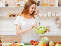 Organic nutrition health care female eating habit. Organic nutrition. Health care. Female eating habit. Smiling young woman with bowl of fresh green salad royalty free stock photos
