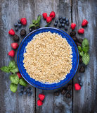 Organic oatmeal in blue bowl with summer berries on wooden background. Top view Stock Photography