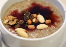 Organic Oatmeal with Jam, Nuts and Raisins. White bowl filled with healthy, organic oatmeal with some red berry jam, almonds and nuts. Delicious breakfast food royalty free stock photography